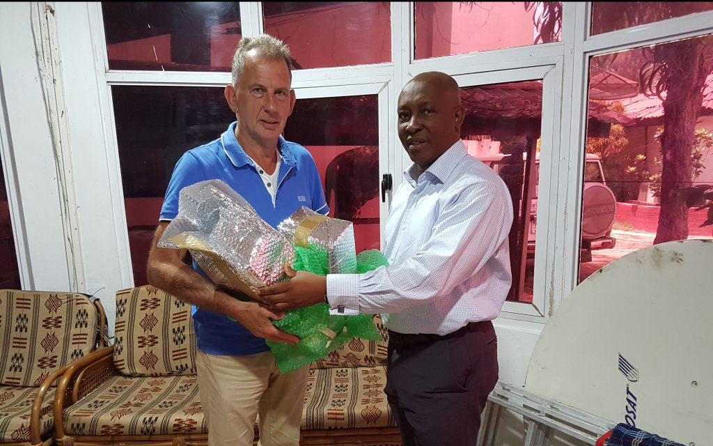 Donald Keus handing a box of insulin to Dr. Patrick E. Turay of the Holy Spirit Hospital in Makeni